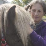 frau moser legt ihre hand auf die stirn eines pferdes